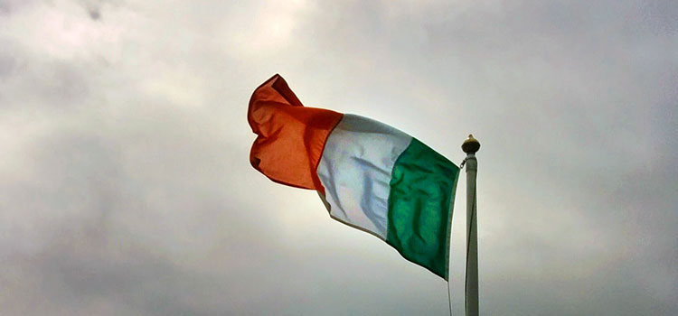 The flag of Ireland flying on a cloudy day.