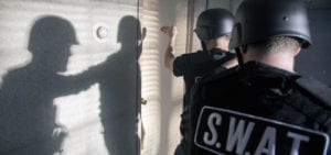 Two SWAT team members preparing to breach a door during a training exercise.