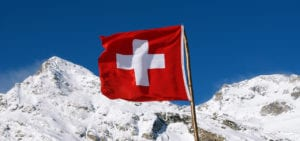 The Swiss flag flies somewhere in the mountains of Switzerland.