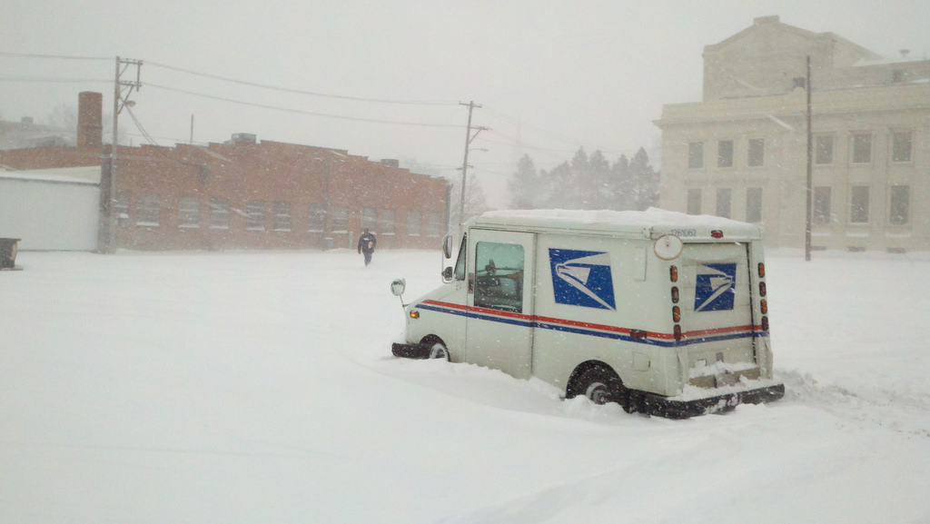 Mail delivery man stuck in snow.,