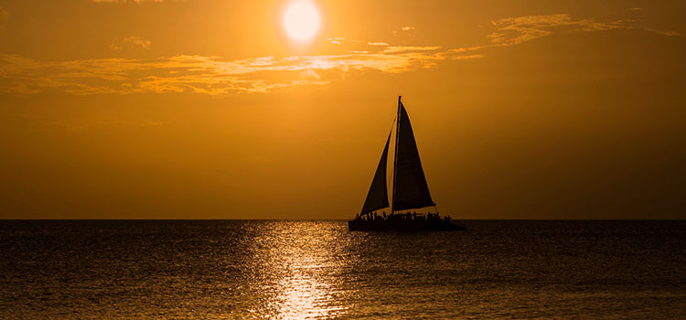 A sailboat silhouetted by the setting sun somewhere in the Cayman Islands.