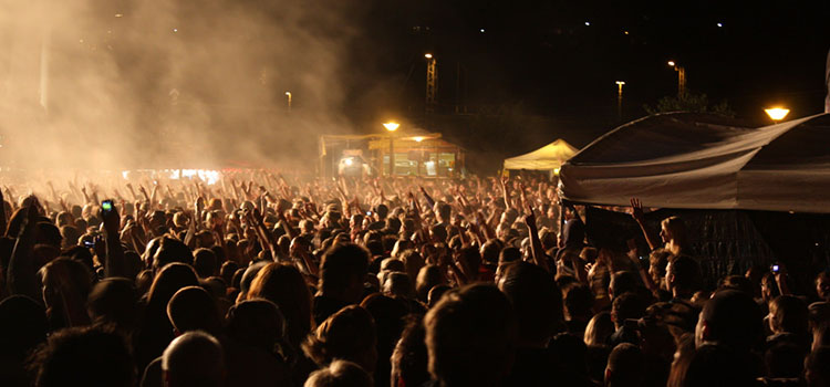 Excited crowd at an outdoor hip hop music concert.