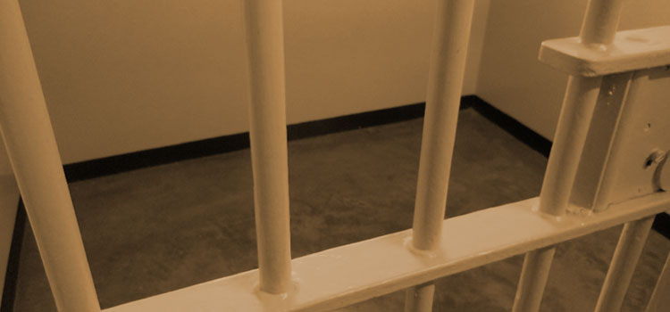 Bars on the door to an unoccupied prison cell.