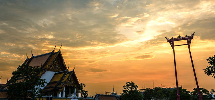 Sunset in Bangkok outside the Buddhist temple Wat Suthat.