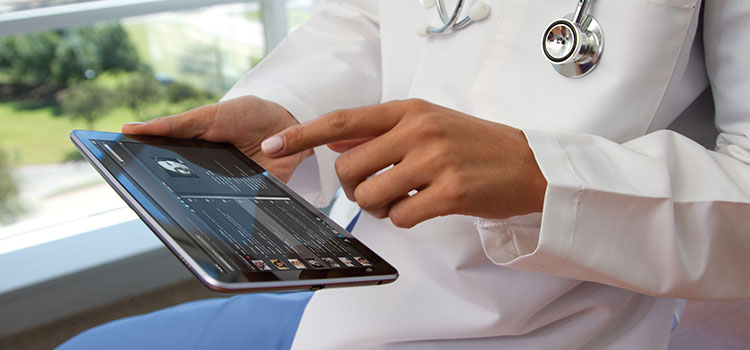 A doctor investigates a patient's medical folder using a touchpad interface.