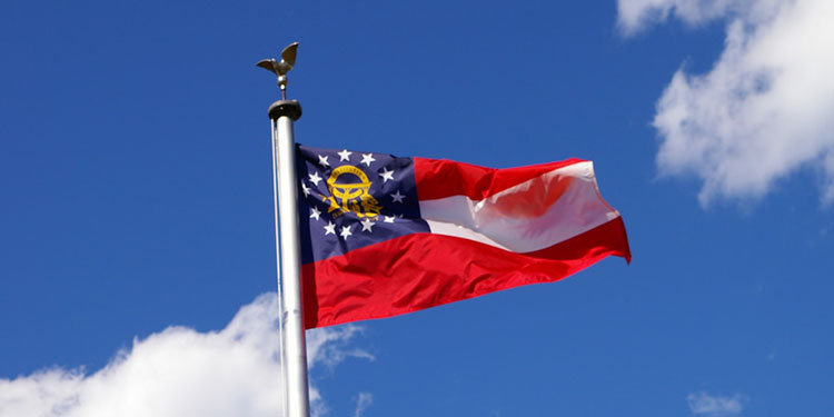 The state flag of Georgia flying on a sunny, blue-skied day.