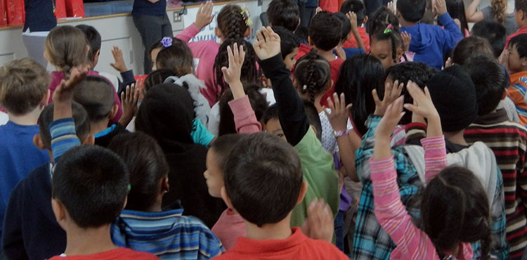 Children raising their hands during a school assembly.