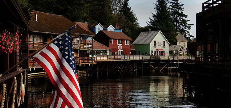 The U.S. flag and Creek Street, in Ketchikan, Alaska