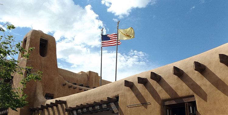 Flags flying on top of an adobe-style building in Santa Fe, New Mexico.