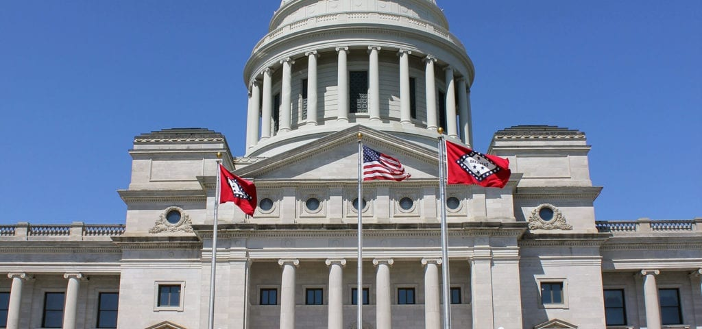 The Arkansas state flag (x2) and the U.S. flag flying in front of the Arkansas Capitol Building.