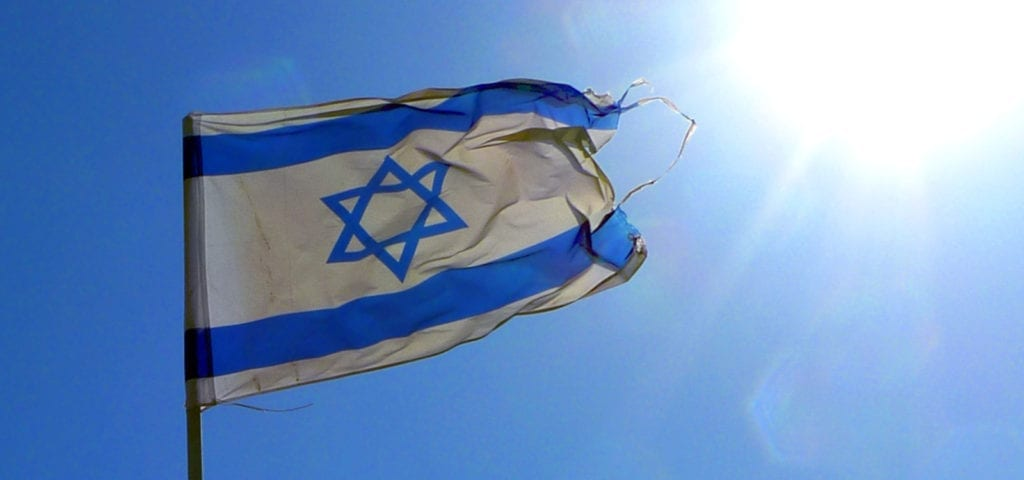 The flag of Israel flies under a sunny, blue sky.