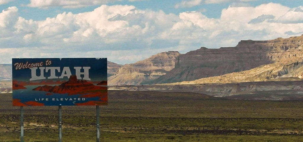 """A """"Welcome to Utah"""" sign alongside the highway in the Southwest plains."""