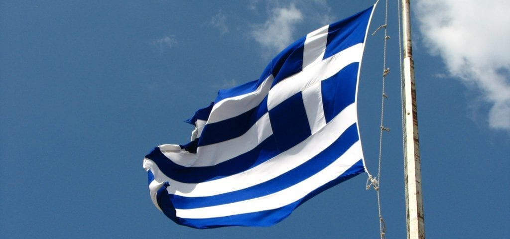 The flag of Greece flying in the sky.