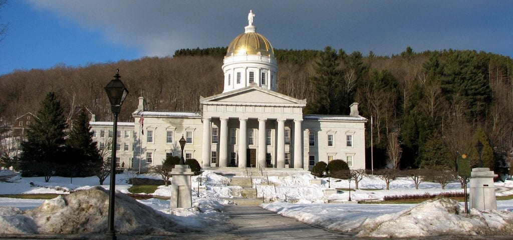 The Vermont capitol building surrounded by snow on a sunny, winter day.