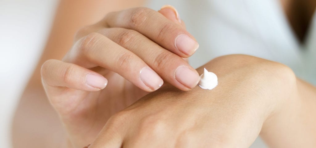 A woman rubs skin care product into the back of her hand.