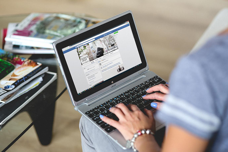 A woman typing information into a Facebook page.