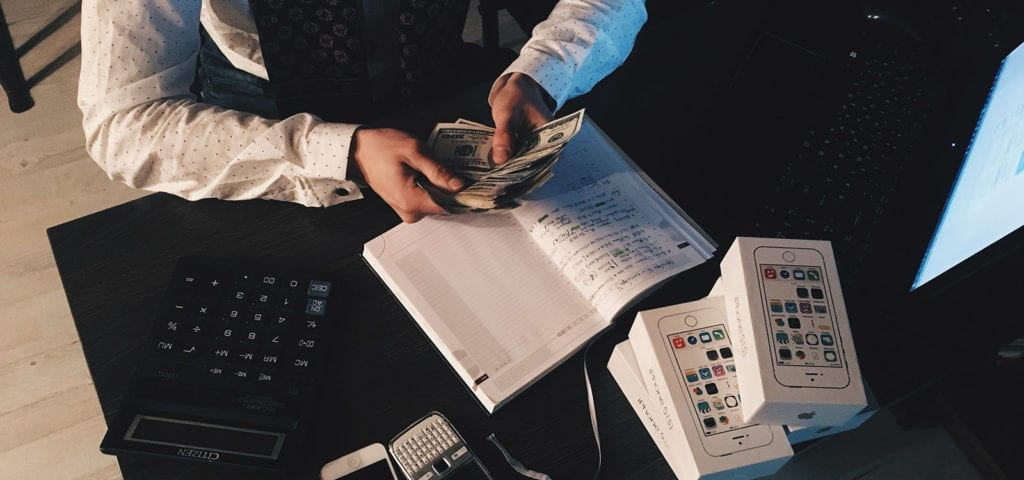 A business person counts cash as part of their taxpaying procedures.