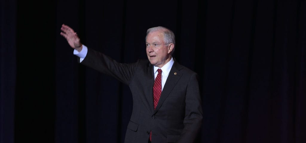Attorney General Jeff Sessions waving his right hand to a crowd of people.