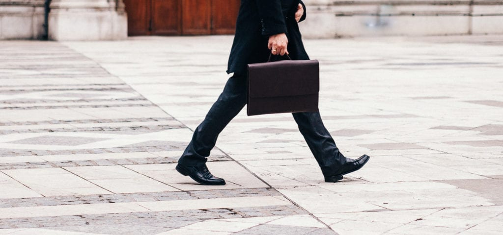 A man wearing a suit and walking across concrete while carrying a briefcase.