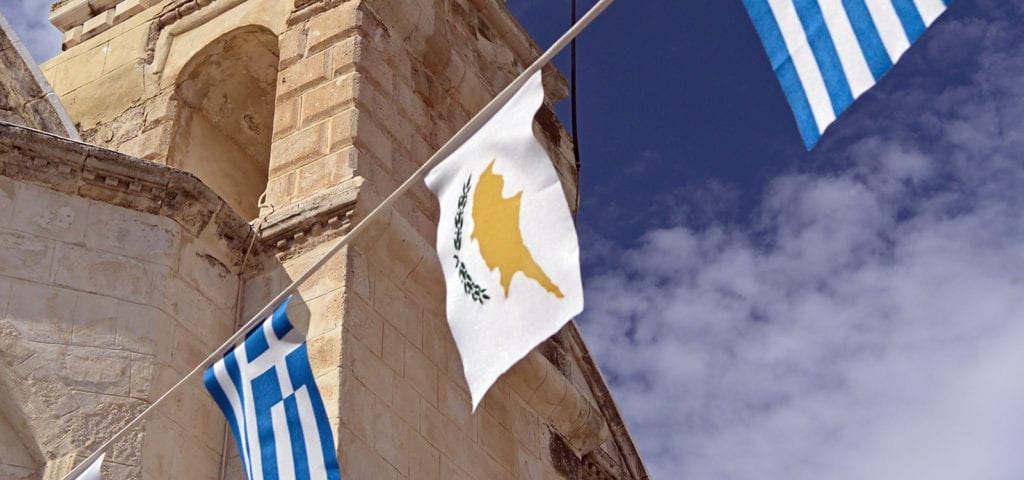 The flag of Cyprus hangs on a line next to the flag of Greece during a day of celebration.