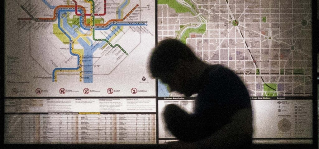 A man's silhouette hunched over in front of a Washington DC metro map.