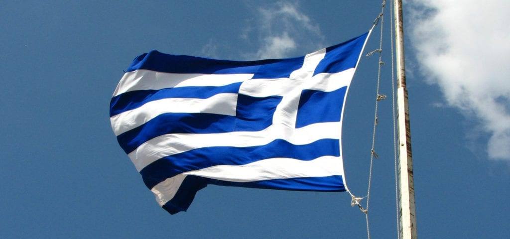 The flag of Greece being blown by wind from the Mediterranean Sea.
