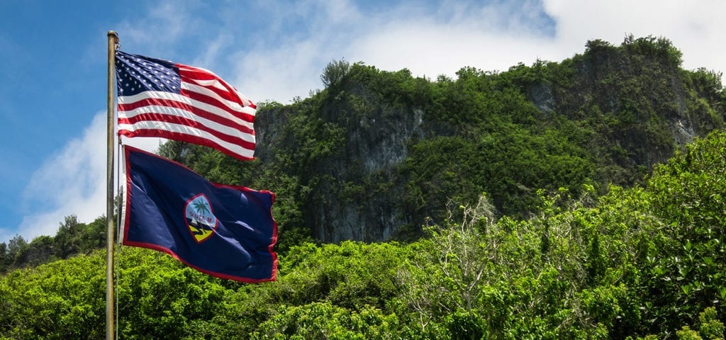 The Guam and U.S. flags pictured at Ritidian Point in the Guam National Wildlife Refuge.