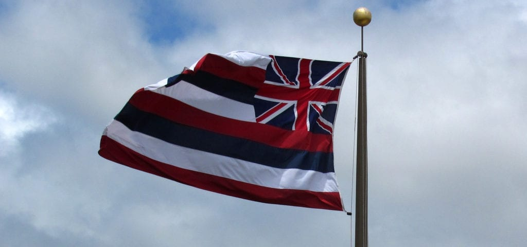 The flag of Hawaii flying above the bay in Honolulu, Hawaii.