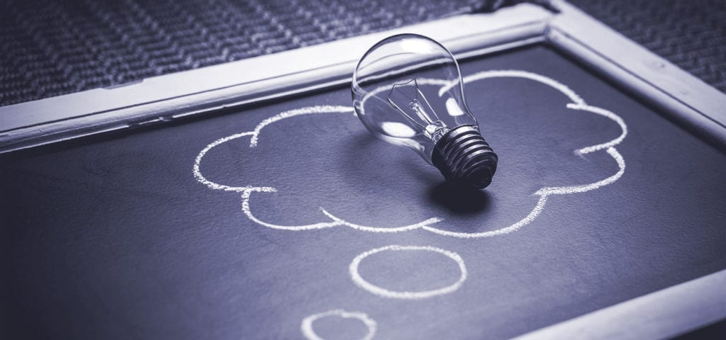 "A symbolic light bulb sits in the middle of a ""thought cloud"" drawn on a chalkboard."