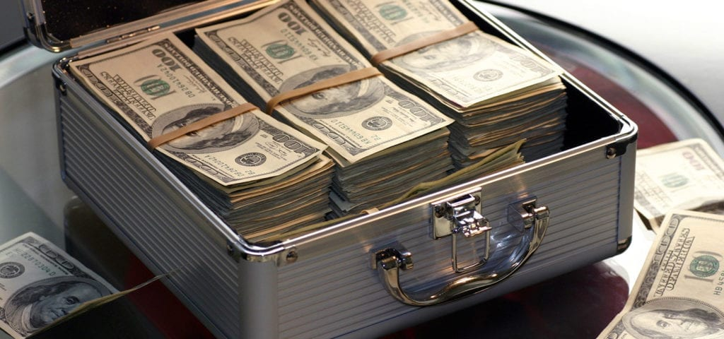 A briefcase stuffed with dollar bills sits open on a glass desk.