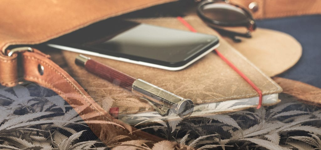 A leather notepad, pen, and cell phone -- the early tools in an entrepreneurial journey.