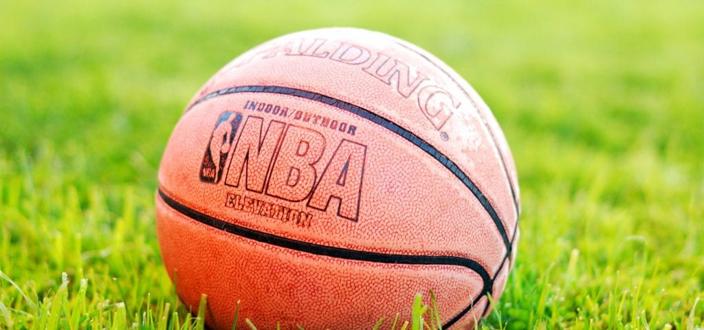 An official NBA Spalding basketball sitting on some grass on a sunny day.