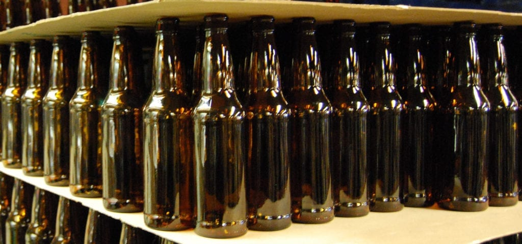 Rows upon rows of bottles inside of a micro brewery.