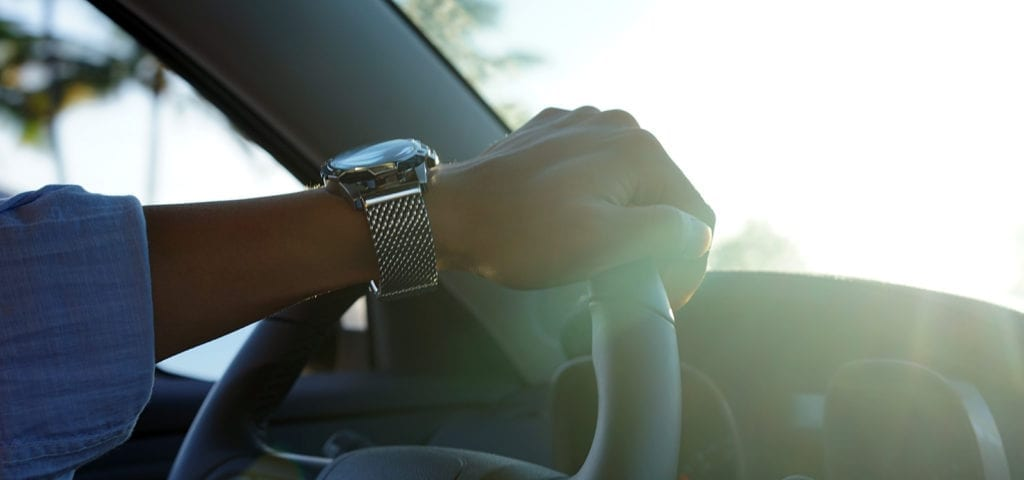 A driver's hand on the steering wheel as they maneuver through traffic.