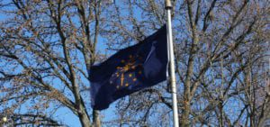 The Indiana state flag flying before a tree on a clear, winter day.