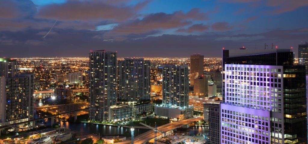 A nighttime photo of the Miami city skyline.