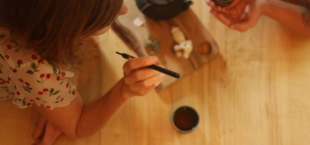 A woman uses a vape pen to consume CBD-rich cannabis oil in conjunction with hot cup of tea.
