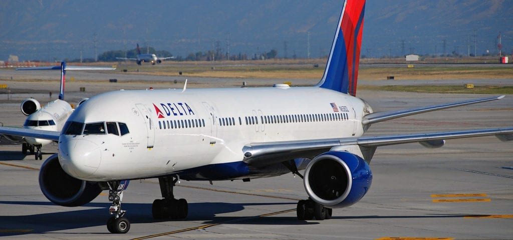 A Delta Airlines aircraft sits on the tarmac, waiting to be next in line for takeoff.