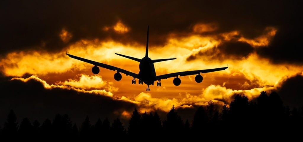 A commercial air plane flies in front of the glowing orange sky of sun down.
