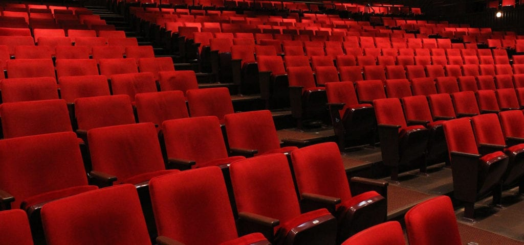 An empty auditorium with red folding cushioned chairs.