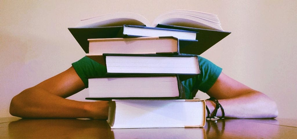 A student resting their head on a table behind a stack of large textbooks.