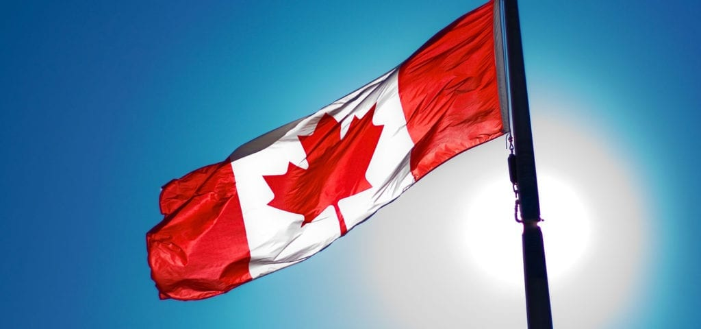 The Canadian flag flying on a blue sky in front of the sun.