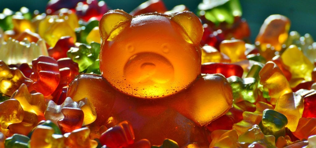 Candy gummy bears in a pile, surrounding the largest candy gummy bear of them all.
