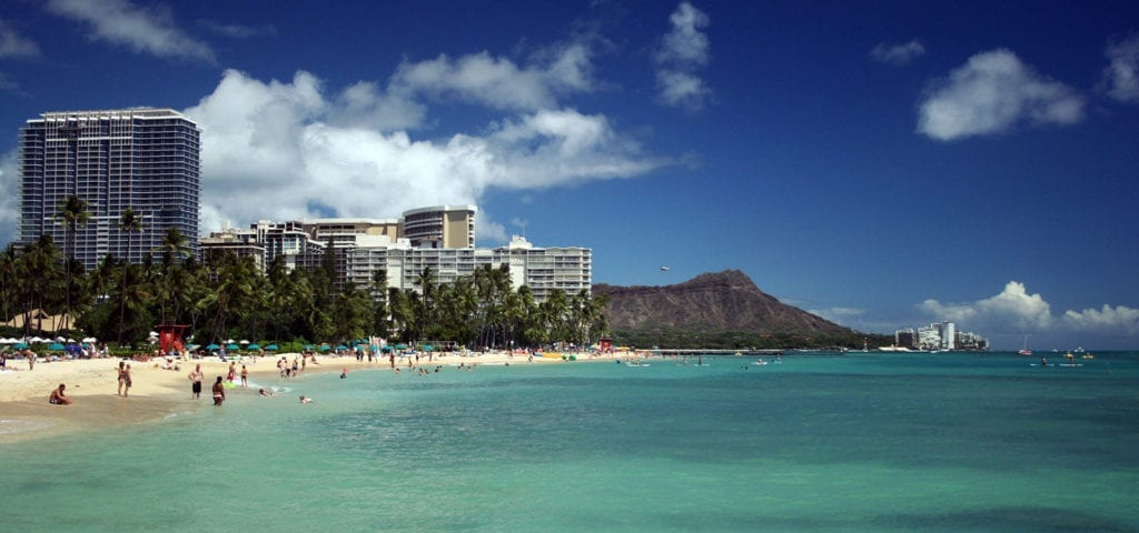 Hawaii vacationers on a beach on a sunny day.