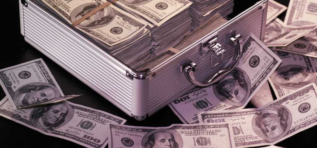 A small suitcase case stuffed with $100 bills in U.S. dollars.