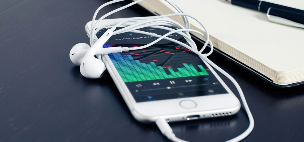Headphones and a digital music player app is open on an iPhone screen.