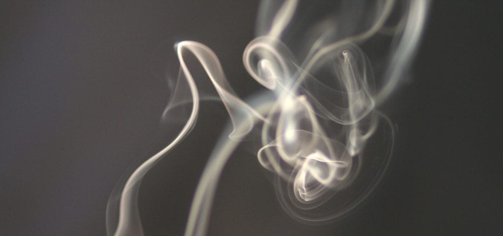 Smoke drifts upwards inside of a dark room.