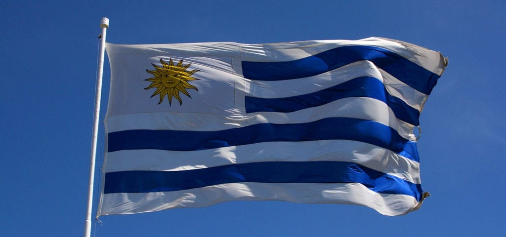 The national flag of Uruguay flying on a windy, cloudless day.
