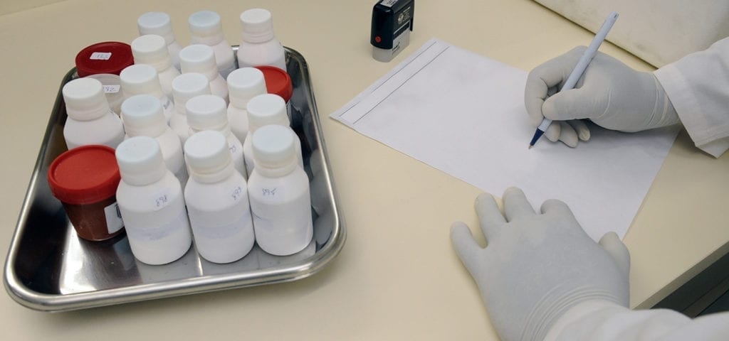 A person wearing a white glove writes on a paper next to some medicine bottles.