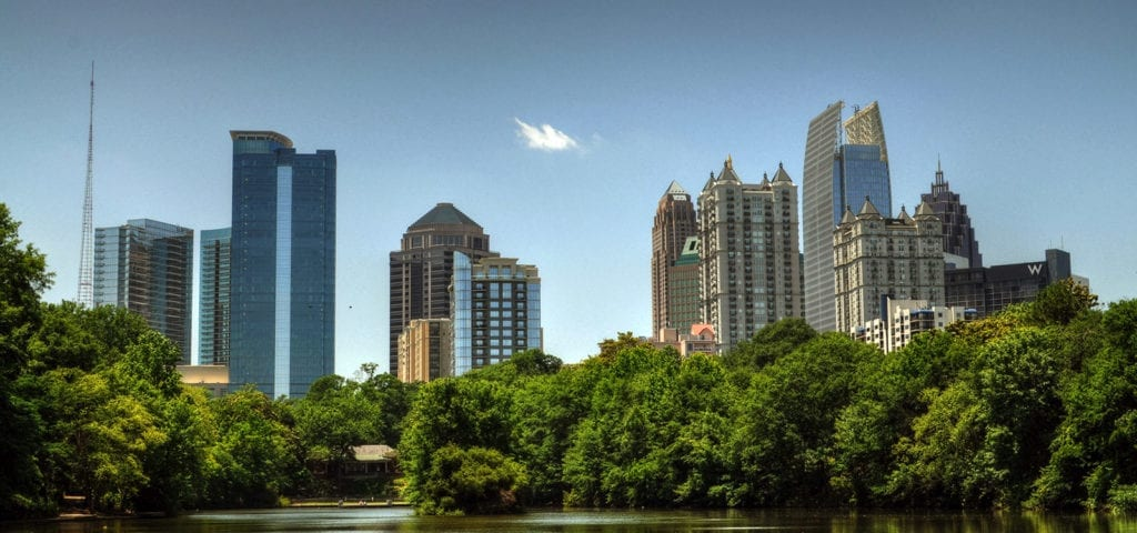 Photograph of Atlanta city poking above the treeline, pictured from a boat on a nearby lake.